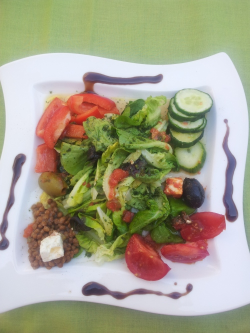 Lollo Bianco and Lollo Rosso, romaine lettuce, bell peppers, cucumbers, olives, tomatoes, lentils and feta cheese on a balsamic vinegar dressing